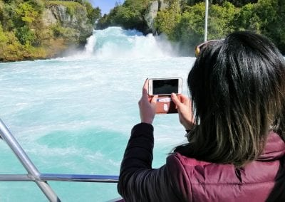 Lady taking photo of Huka Falls from boat