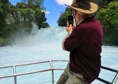 Man taking photo of Huka Falls from front viewing platform